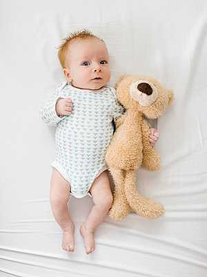 Baby boy (2-5Êmonths)Êlying on bed with teddy bear - p1427m2186343 by Jessica Peterson