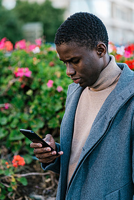 Man wearing jacket using mobile phone while standing at park - p300m2251046 by Ezequiel Giménez