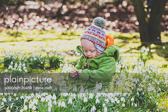 Baby girl sitting on a meadow covered with snowdrops - p300m2120450 by Irina Heß