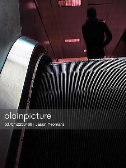 Figure on escalator - p378m2235466 by Jason Yeomans