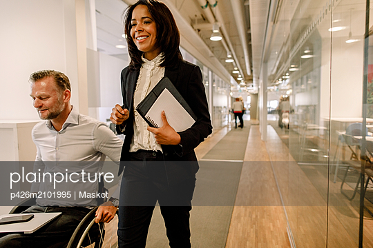 Smiling businesswoman with disabled male manager in office corridor - p426m2101995 by Maskot