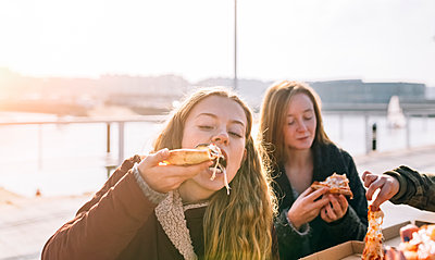 Friends eating pizza outdoors - p300m1228374 by Marco Govel