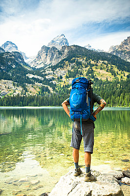 A backpacker stops at a lake to look at the mountains. - p343m1184703 by Rob Hammer