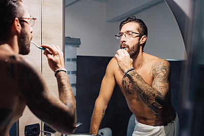 Mid adult man with tattoos brushing teeth at bathroom mirror - p924m2097354 by Eugenio Marongiu