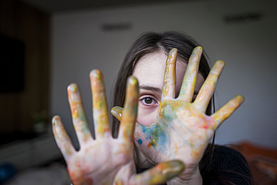 Close up portrait girl with finger paint covering hands - p1023m2208276 by Tom Merton
