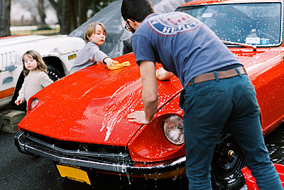 Little kids helping their father wash a classic old red car outside - p1166m2261975 by Cavan Images