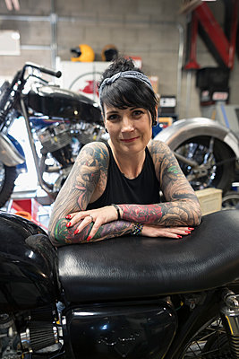 Portrait confident female motorcycle mechanic with tattoos in auto repair shop - p1192m1447393 by Hero Images