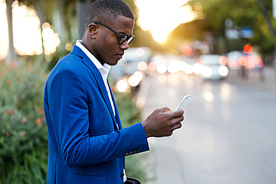 Young businessman wearing blue suit jacket and using smartphone - p300m2114601 von Josep Suria