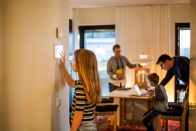 Girl using digital tablet on wall with family in background at smart home - p426m2195371 by Maskot