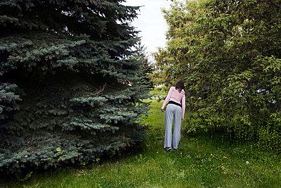 Woman hiding behind trees - p8360104 by Benjamin Rondel