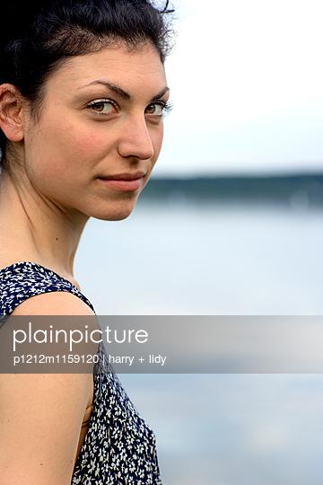 Portrait einer jungen Frau am Ufer - p1212m1159120 von harry + lidy