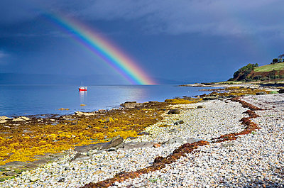 Rainbow above Fishing Boat on Rocky Shore - p1072m836351 by chinch gryniewicz