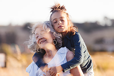 Grandson embracing grandmother while standing on field - p1166m1489573 by Cavan Images