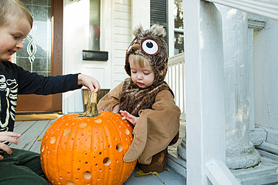 Two children examine jack o lantern on front porch during Halloween - p1166m2084468 by Cavan Images