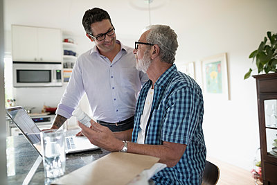 Son helping senior father reorder prescription medications at laptop in kitchen - p1192m1529672 by Hero Images