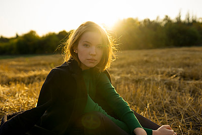 Junge Frau auf einem Stoppelfeld in der Abendsonne - p1646m2249821 von Slava Chistyakov