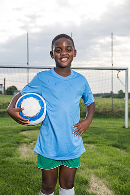 Portrait of smiling young football player holding ball on football ground - p300m1581427 by Fotoagentur WESTEND61