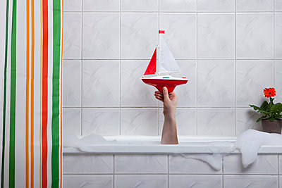 A human hand sticking out of a bathtub holding a toy boat - p3019975f by Tw ins