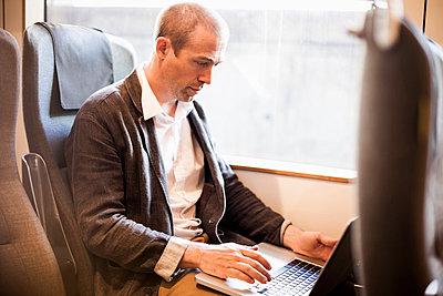 Mature businessman using laptop in train - p426m844675f by Maskot