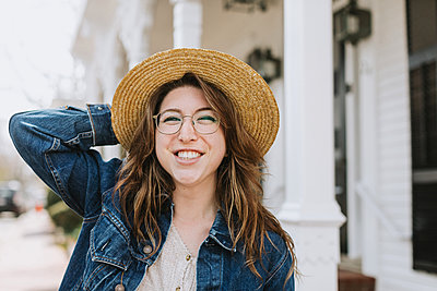 Young woman strolling on sidewalk wearing straw boater, portrait, Menemsha, Martha's Vineyard, Massachusetts, USA - p924m2058138 by Lena Mirisola