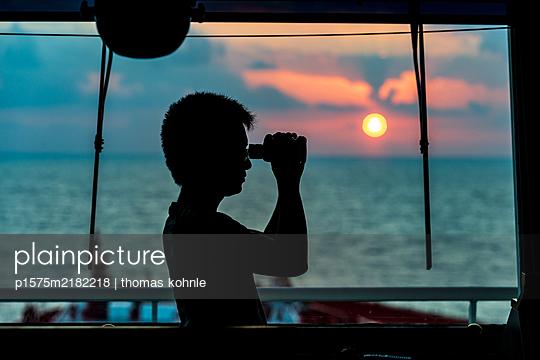 Kapitän blickt durch ein Fernglas - p1575m2182218 von thomas kohnle