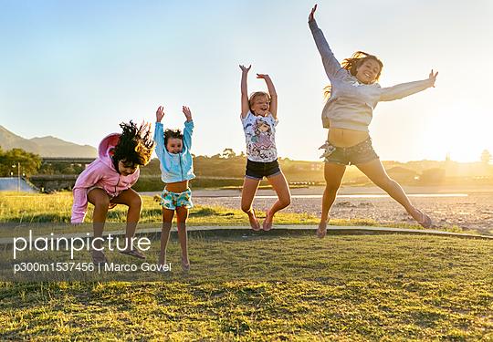 plainpicture | Photo library for authentic images - plainpicture p300m1537456 - Four happy girls jumping in... - plainpicture/Westend61/Marco Govel