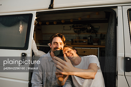 Gay couple taking selfie on smart phone while sitting at doorway of motor home - p426m2296160 by Maskot