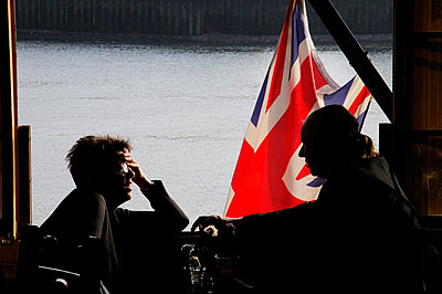 Couple in a pub on the river Thames in London, with a Union Jack flag visible through the open window - p1072m829398 by Neville Mountford-Hoare