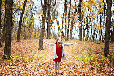 Young Red Hair Girl Playing Outside in Fall Leaves - p1166m2147043 by Cavan Images