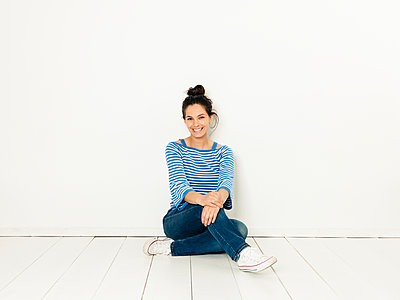 Beautiful young woman with black hair and blue white striped sweater sitting on the ground in front of white background - p300m2103073 von Epiximages