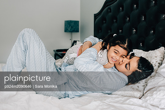 Girl and mother hugging on bed in morning - p924m2090646 by Sara Monika