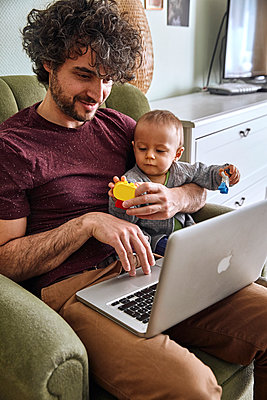 Father with laptop and baby boy, Stay at home due to Covid-19 - p1146m2182014 by Stephanie Uhlenbrock