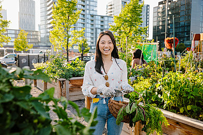Portrait happy, carefree young woman harvesting fresh vegetables in urban community garden - p1192m2130338 by Hero Images