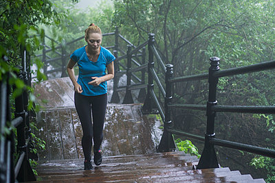 Girl running in the rain - p1362m1227702 by Charles Knox