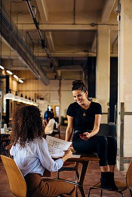Two happy young businesswomen with smartphone in loft office - p300m2144799 by Sofie Delauw