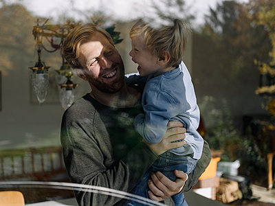 Happy father carrying son at the window at home - p300m2166587 by Kniel Synnatzschke