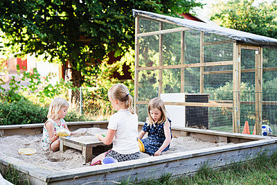 Girls playing in sandpit - p312m2079972 by Anna Johnsson