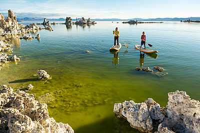 A woman and her daughter stand up paddleboarding on Mono Lake,  Lee Vining, California. - p343m1168428 by Kennan Harvey
