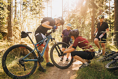 Friend assisting woman in repairing mountain bike at forest - p426m2036758 by Katja Kircher