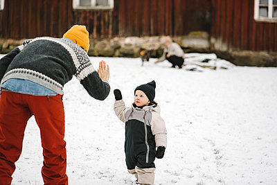 Rear view of mother giving high-five to daughter during winter - p426m2284823 by Maskot