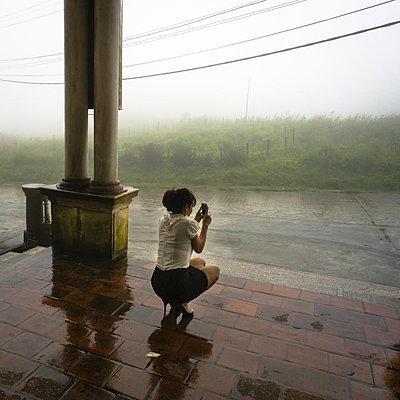 A woman squats on the ground to shoot a photo of a misty scene with a camera phone - p934m1022248 by Sebastien Loffler