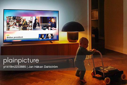 Toddler walks by TV with Biden inauguration - p1418m2233885 by Jan Håkan Dahlström