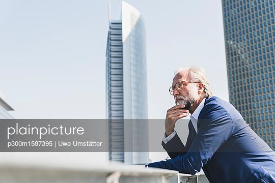 Serious mature businessman in the city looking around - p300m1587395 von Uwe Umstätter