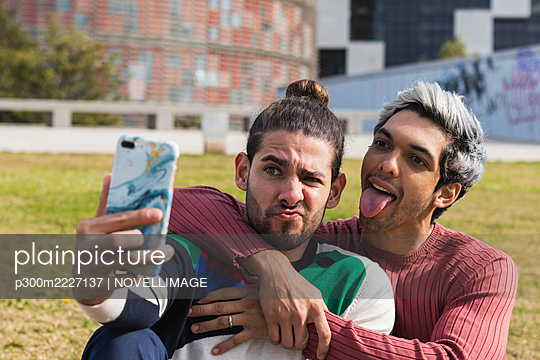 Man with male partner sticking out tongue while taking selfie through smart phone in park - p300m2227137 by NOVELLIMAGE