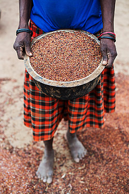 Africa, Uganda, Woman with sorghum - p1167m2283433 by Maria Schiffer