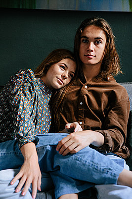 Teenage couple in love on a sofa - p1640m2242137 by Holly & John