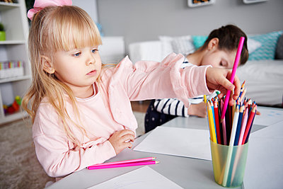 Portrait of little girl drawing with coloured pencils in the living room - p300m1581178 by gpointstudio