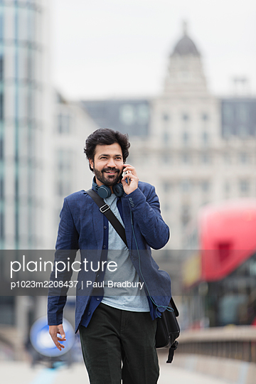 Businessman talking on smart phone in city - p1023m2208437 by Paul Bradbury