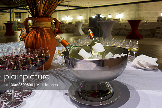 Wine bottles in metal ice bucket. Cooler with ice cubes. Wine glasses. - p1100m2300896 by Mint Images