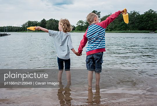 brother & sister holding hands playing together in the sea on vacation - p1166m2129949 by Cavan Images